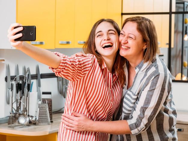 행복한 가족 관계. 어머니와 딸이 함께 시간을 즐기고, 집 부엌에서 셀카를 찍고, 포옹, 웃고.