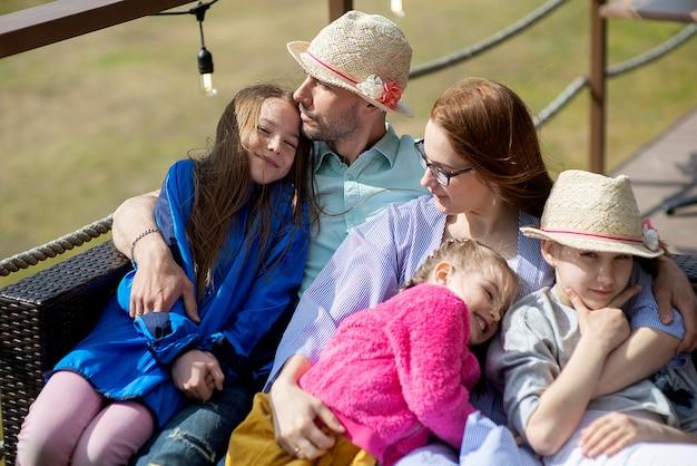 Счастливая семья отдыхает на открытой террасе летнего ресторана