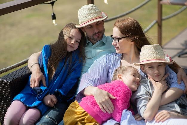 Счастливая семья отдыхает на открытой террасе в летнем ресторане