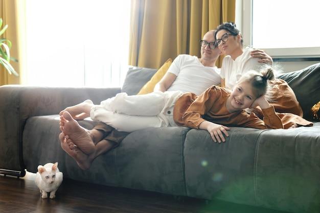 幸せな家族はリラックスして家でテレビ番組を見ています
