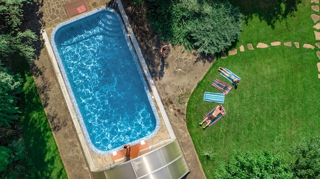 Happy family relaxing by swimming pool, aerial drone view from above of parents and kids have fun on vacation