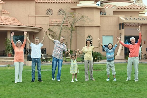 Happy family relaxing at vacation resort with hands up