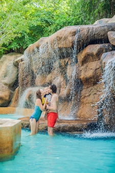 Happy family relaxing under a waterfall in aquapark
