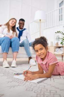 거실에서 쉬고 있는 행복한 가족. 어머니, 아버지, 그리고 그들의 딸은 집에서 함께 포즈를 취하고 좋은 관계를 유지합니다. 엄마 아빠와 여자 아이