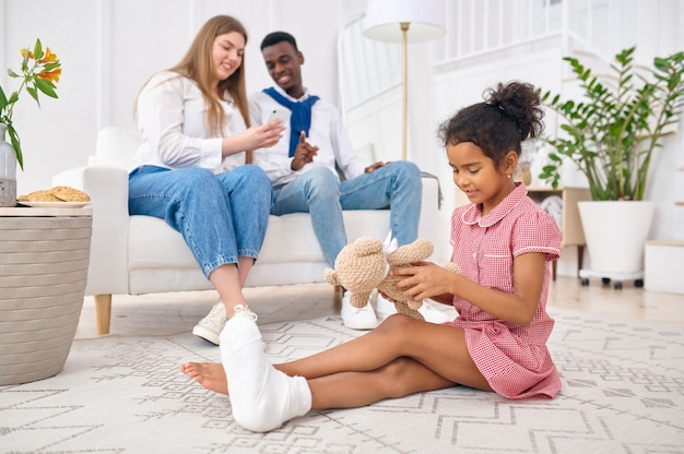 Happy family resting in living room. mother, father and their daughter poses at home together, good relationship. mom, dad and female child, photo shoot in house