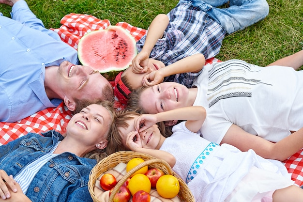 Happy family resting on picnic. enjoying and lying on checkered plaid in meadow. adults and children look at the sky.