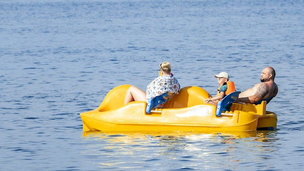 Happy family rides a catamaran on the sea