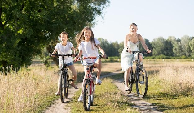 Happy family riding on bicycles in meadow at sunny day