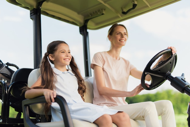 Happy family riding by golf car mum and daughter.