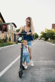 Счастливая семья езда скутер по соседству на дороге.