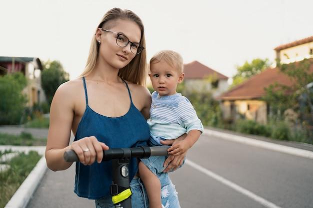 道路上の近所の幸せな家族乗馬スクーター。