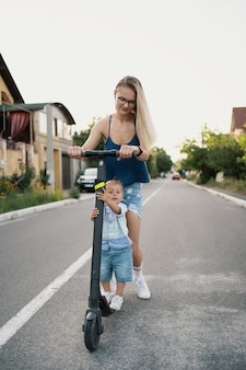 Happy family riding scooter in the neighborhood on the road.