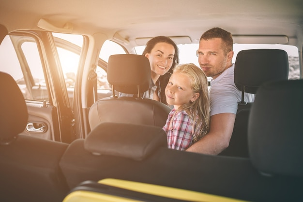 Happy family on a road trip in their car. dad, mom and daughter are traveling by the sea or the ocean or the river. summer ride by automobile.