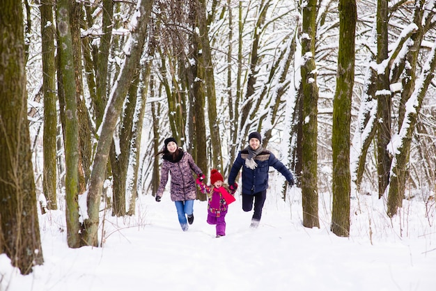 Happy family run in winter forest