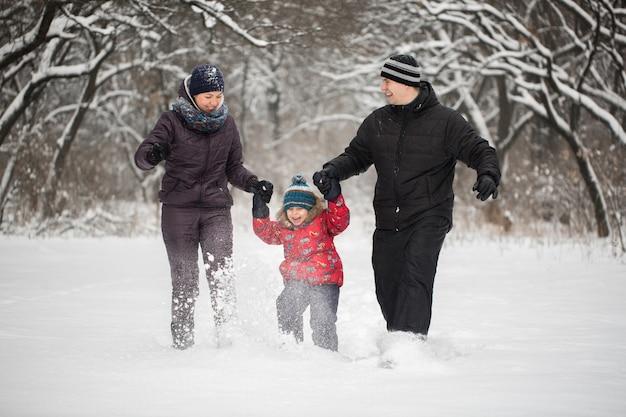 冬に雪の上を走っている幸せな家族