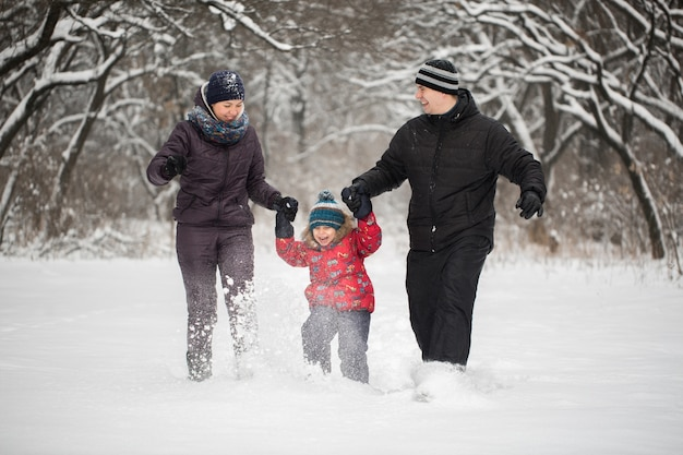Happy family running on snow in winter
