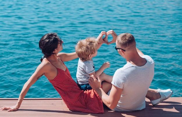 바다에서 손의 행복 한 가족 모양 심장입니다. 가족 가치로서의 사랑과 신뢰.