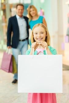 幸せな家族の買い物。小さな女の子が買い物袋を見せて笑っている間、ショッピングモールで陽気な家族の買い物
