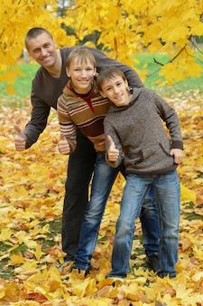 幸せな家族は秋の公園で親指を立てる