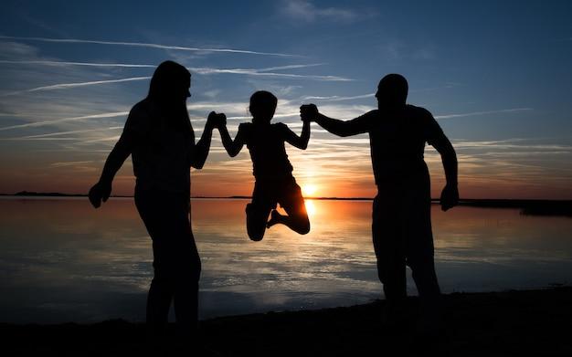 Happy family silhouette at the beach