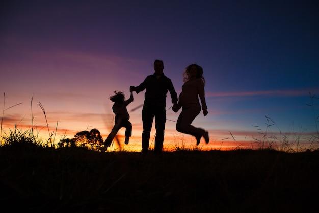 일몰에 점프하는 행복 한 가족 실루엣