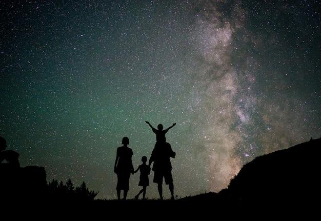 天の川の美しい夜空と星の幸せな家族のシルエット