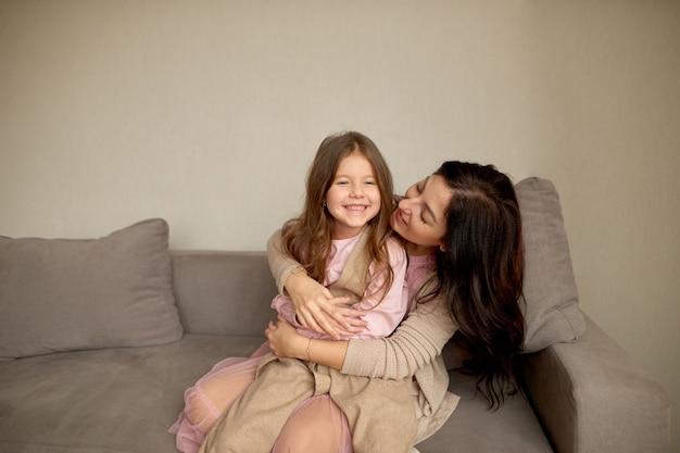 어린 아이 소녀 재미 연주와 함께 행복 한 가족 싱글 엄마는 기쁨을 껴안고 포옹을 느낍니다. 사랑으로 꽉 안아주고