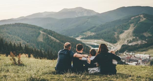 幸せな家族が山を眺めて座り、子供たちを腕に抱きしめている。日没。クローズ アップ、背面からの眺め。アクティブなライフスタイル。旅行します。山の平和とインスピレーション。横向きの写真