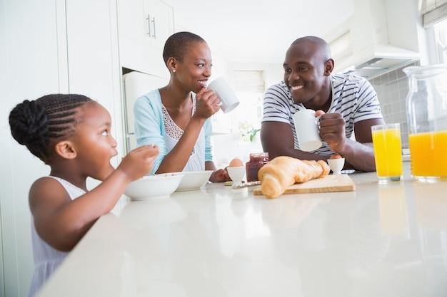 幸せな家庭に座って朝食を取る
