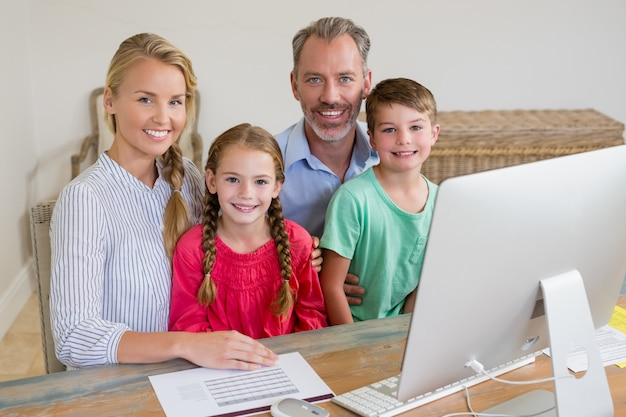 コンピューターを机に座って幸せな家族