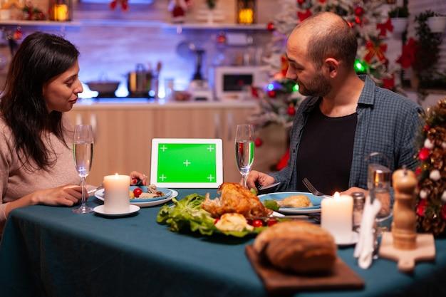 크리스마스 장식 주방의 식탁에 앉아 있는 행복한 가족