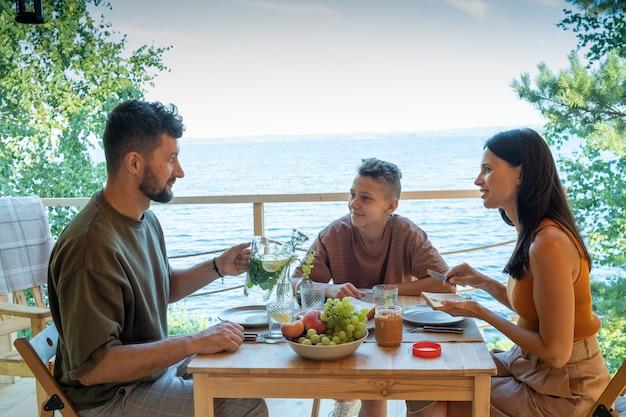 Счастливая семья, сидя за обслуживаемым столом во время обеда или завтрака на открытом воздухе