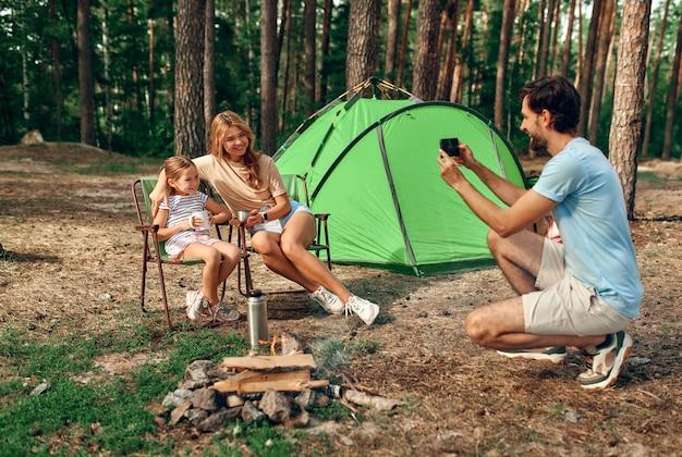 Счастливая семья, сидя у костра возле палатки в сосновом лесу на выходных. мужчина фотографирует на телефон жену и дочь. походы, отдых, походы.