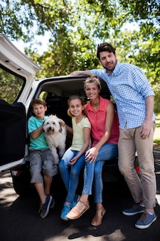 Happy family sitting in car trunk with their dog