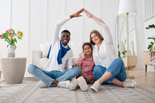 Happy family sitting on the floor in living room