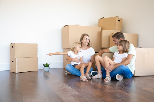 Happy family sitting on floor in new home near cardboard boxes