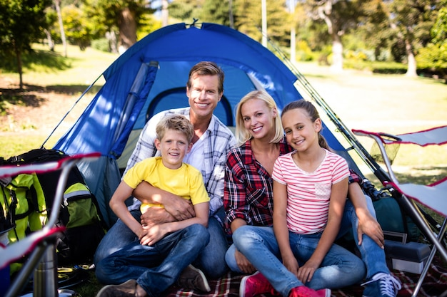 Happy family sitting in front of a tent