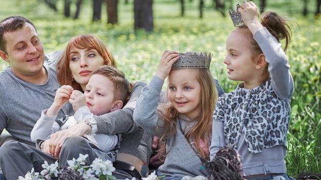 ピクニック中に空き地に座っている幸せな家族。家族の休日の概念