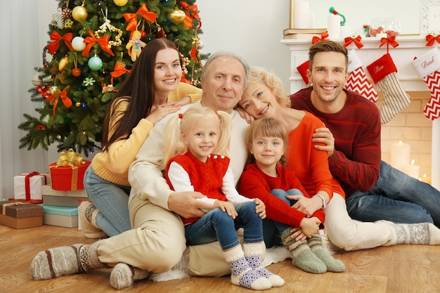 Happy family sitting in living room decorated for christmas