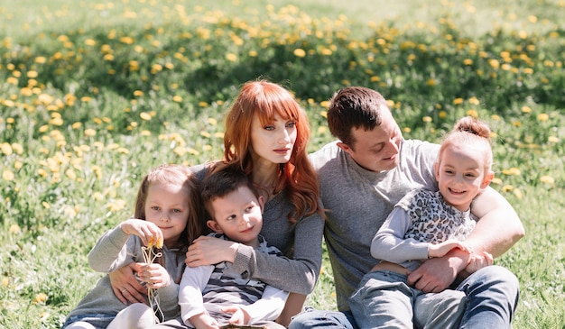 Happy family sitting in a meadow on a sunny day. good time