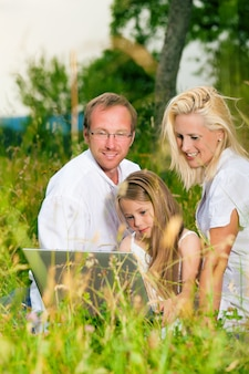 Happy family sitting in meadow with laptop computer