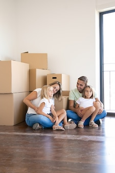 Happy family sitting near carton boxes in living room of new home