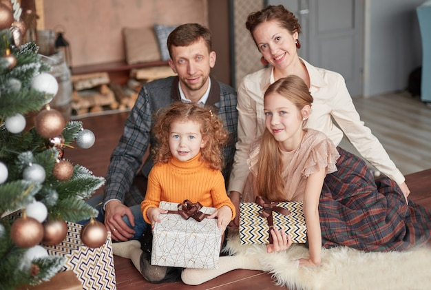 Happy family sitting near christmas tree on christmas evening.