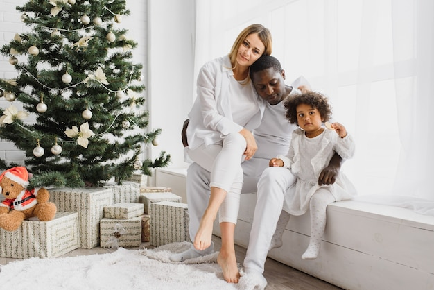Happy family sitting near the christmas tree