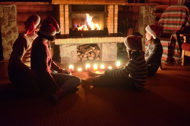 Happy family sitting near fireplace at home and celebrating christmas and new year, parents and children in santa hats