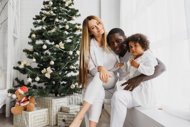 クリスマスツリーのそばに座って幸せな家族