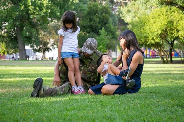 都市公園の芝生の上に座って幸せな家族。軍服を着た白人の中年の父親、笑顔の母親と子供たちが牧草地で一緒にリラックス。家族の再会、週末、帰国のコンセプト
