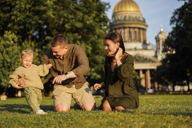 상트페테르부르크 성 이삭 대성당 앞 잔디에 앉아 있는 행복한 가족. 걷는 법을 배우는 어린 소년
