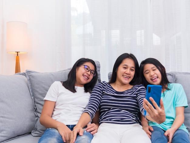 リビングルームのソファに座って幸せな家族が一緒に携帯電話で誰かと話し、スマートフォンでかわいい小さな子供のビデオ通話を見せている笑顔の母親が家族と話します。