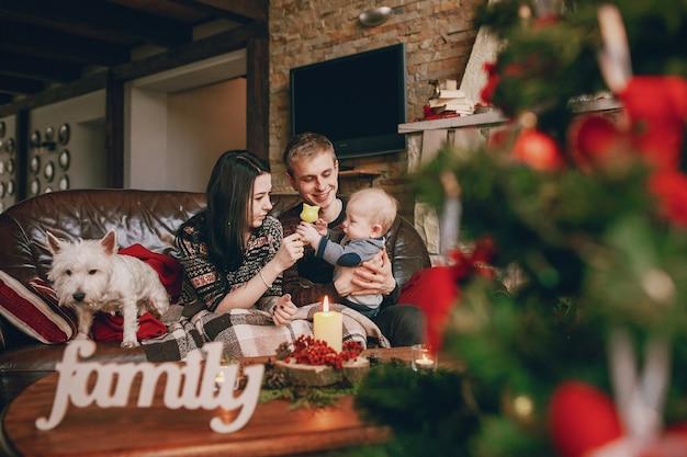 正面のデフォーカスクリスマスツリーと単語「家族」でソファに座って幸せな家族